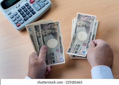 japanese yen notes. hands counting money in japanese currency