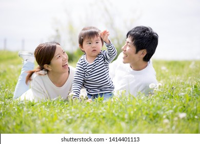 Japanese young family playing on the grass in the park