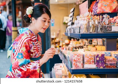 Japanese young girl wearing kimono and choosing handkerchief in the shop. pretty lady with traditional dress shopping. Japanese teenager lifestyle.