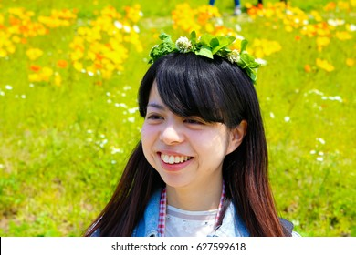 japanese young lady with flower crown in flower garden