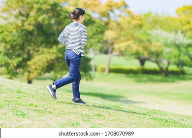Japanese young woman running at park in spring