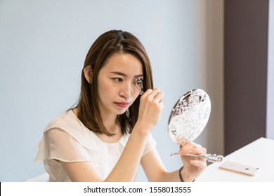 japanese young woman uses eyelash curler