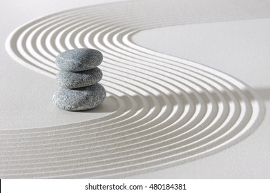 Japanese zen garden in white sand with stacked stones