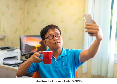 Japanese,Chinese,korean,Young formal man  with coffee taking selfie with smartphone in light modern office.