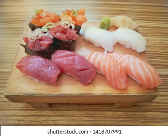 Japanese-style sushi set consisting of sushi, raw salmon on rice ball, raw tuna rice ball, raw squid are served on wooden plates. The background is a wooden table.