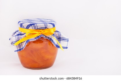 A jar of apricot jam on a white background. Copy space