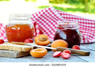 Jar of apricot and strawberry jam, fresh apricots and strawberries, knife and toast bread with butter on wooden table, red checkered tablecloth in background in summer garden