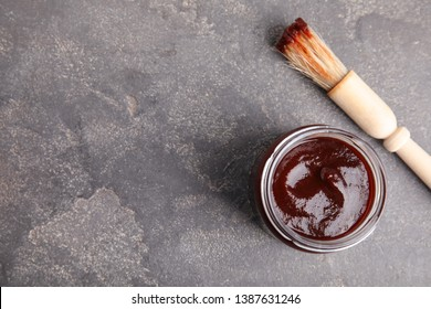 Jar with barbecue sauce and brush on grey background, flat lay. Space for text