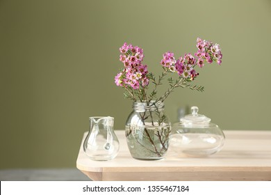 Jar with beautiful flowers on table against color background