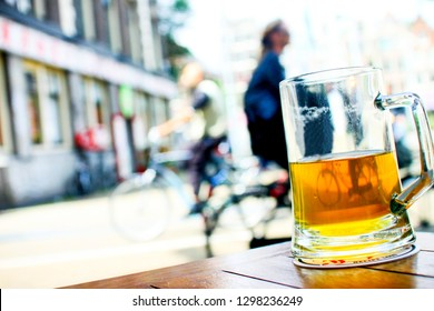 A jar of beer over a table in a terrace in Amsterdam, with reflections of a cycler across the street inside