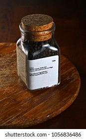 A jar of black peppercorns on dark wood background, shallow focus