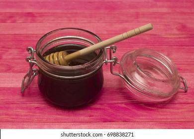jar buckwheat honey on pink wooden table