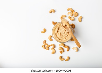Jar of cashew butter with cashew nuts on the white  background