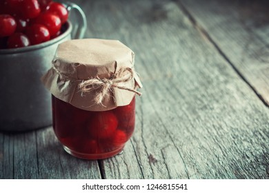 Jar of cherry jam and mug of ripe cherries not in focus on wooden table. Copy space for text.