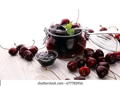 Jar of cherry jam, sour cherries and spoon