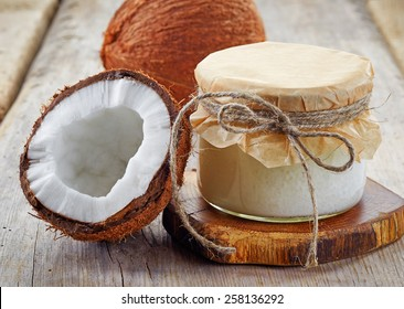 jar of coconut oil and fresh coconuts on wooden table