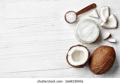 Jar of coconut oil and fresh coconut on white wooden background, top view