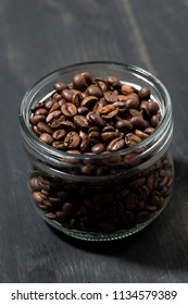 jar of coffee beans on a wooden background, concept photo, vertical closeup