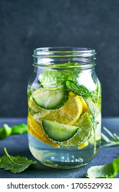 Jar of cold infused water (lime, lemon, cucumber, mint, basil, rosemary) on dark stone background. Copy space
