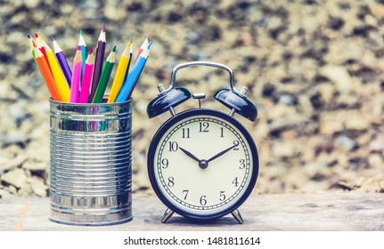 Jar with colored pencils. Color pencils and alarm clock. Back to school background