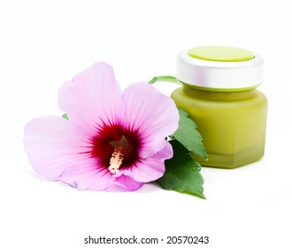 Jar for cosmetic cream and flower isolated on white