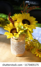 Jar covered in burlap and lace filled with faux sunflowers set on an outdoor table covered with burlap and white fabric