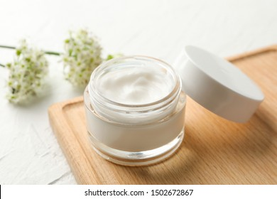 Jar with cream, allium flowers and board on white background, closeup