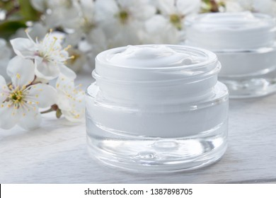 A jar of cream close-up, face cream surrounded by cherry flowers. Face Cream in Glass Jar