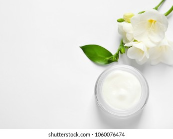 Jar of cream and flowers on white background, top view. Professional cosmetic products
