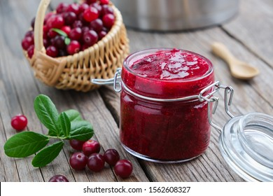 Jar of crushed cranberries for sauce or jam and basket of bog berries on background.