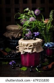 Jar of delicious homemade black currant curd (jam) on dark background