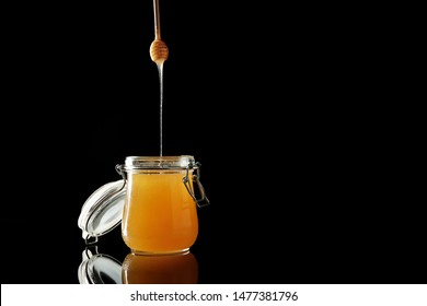 Jar and dipper with tasty honey on dark background