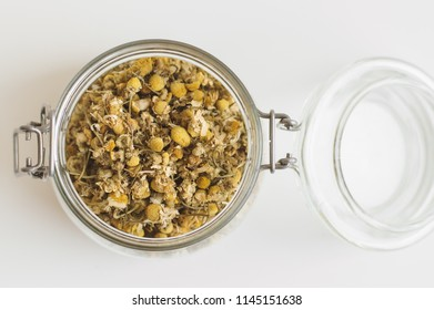 Jar with dried chamomile flowers. Herbal tea, top view