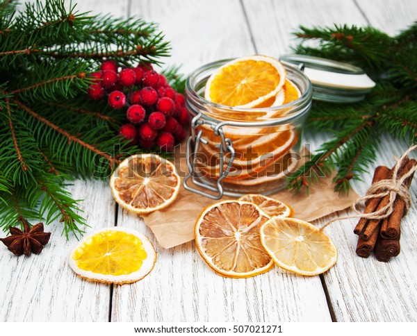 Jar with dried oranges and christmas decorations