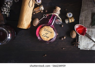 A jar with Elixir of Love on wood table. Spoon with red sweet heart, old books, flasks, bottles. Valentines Day and Love concept