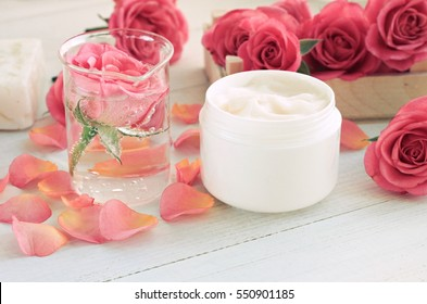 Jar of facial beauty cream, infused floral attar in glass test vial, fresh roses, pink petals, white wooden table. Soft focus, toned.