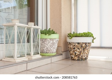 Jar of flowers and white candlestick on a balcony