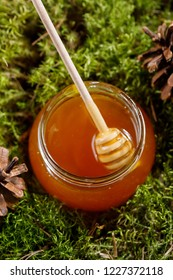 A jar of fragrant sweet honey and a honey stick in it.