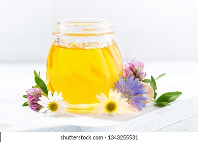 jar with fresh flower honey on a white table, closeup