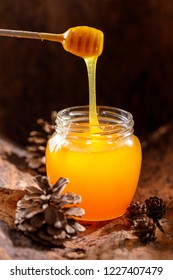 A jar of fresh, fragrant honey flowing down from a wooden stick. Close-up.