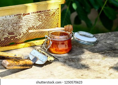 Jar of fresh honey with assorted tools for beekeeping, a wooden dispenser and tray of honeycomb from a bee hive in a still life on a wooden table outdoors with copy space.