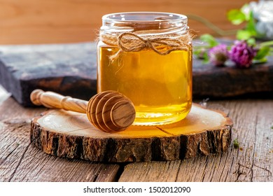 jar of fresh honey with honey dipper on  wooden slice and  boards close-up  with flowers on background