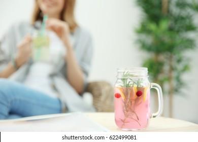 Jar of fresh lemonade and blurred woman on background
