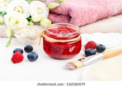 Jar of fruit beauty care mask of mashed red raspberies, flowers and towels spa background, fresh berries for skin exfoliation.