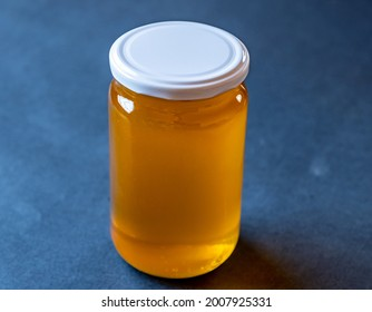 a jar full of honey alone with antique blue background