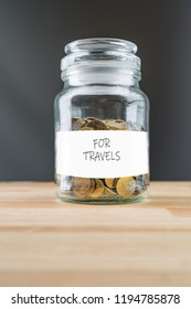 Jar with golden coins on natural wooden background. Money saving for travels abstract concept.