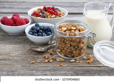 jar with granola, milk, and fresh berries on the wooden background, horizontal