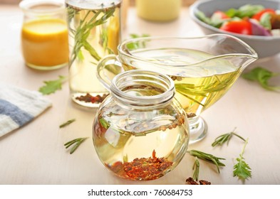 Jar and gravy boat with tasty salad dressings on table