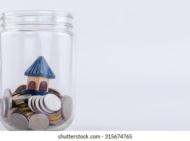 Jar with half of coin and small house concept