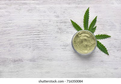Jar of hemp lotion on wooden background